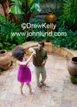 Picture of a happy ethnic couple dancing outdoors in a garden barefoot and having loads of fun.
